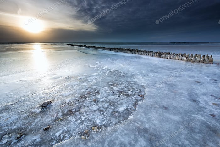 frozen breakwater on big lake in winter
