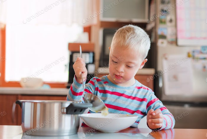 A handicapped down syndrome child pouring soup into a plate indoors.
