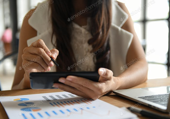 Woman hand are using a pen on a mobile phone screen. Graphs and laptop placed on the desk.