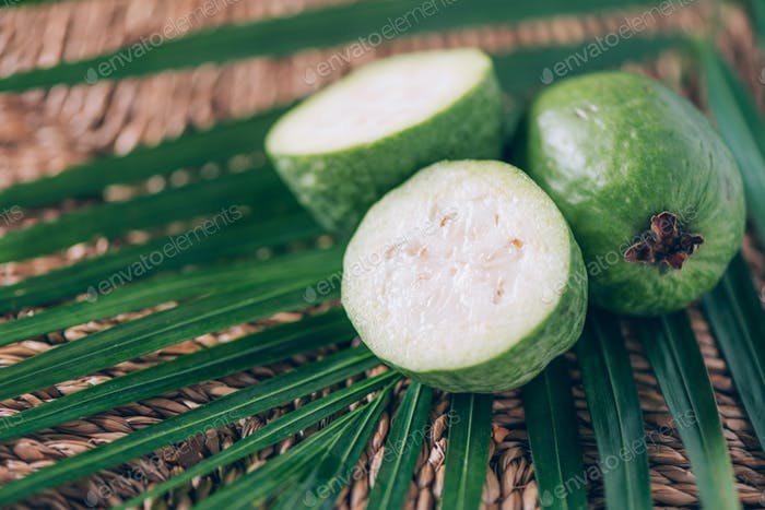 Tropical fruit feijoa over palm leaves on rattan background. Copy space. Acca sellowiana. Creative
