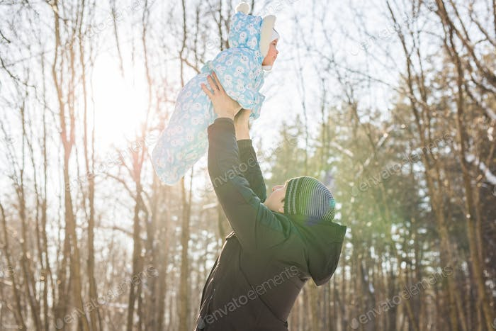 Happy father playing with little child son boy in winter nature
