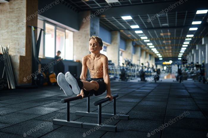 Boy doing ABS exercise on uneven bars in gym