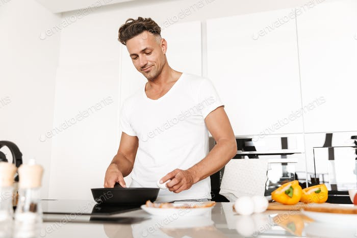 Attractive man cooking eggs for breakfast