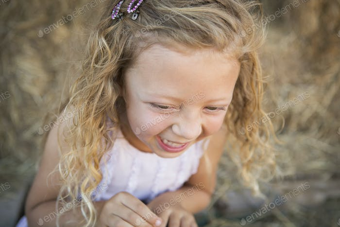 A young girl in a barn laughing.