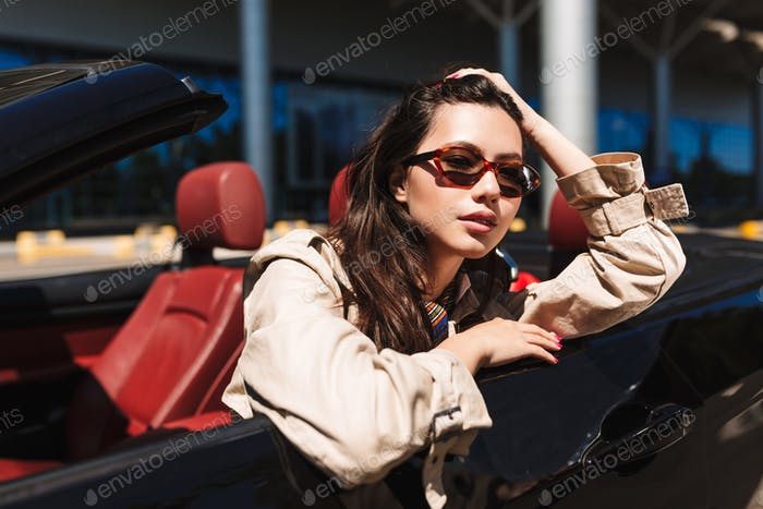 Beautiful girl in sunglasses leaning on cabriolet car door while
