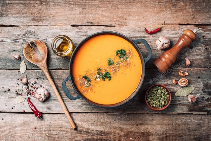 Pumpkin soup on in iron pot on wooden background. Top view. Copy space