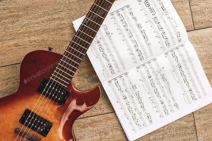 The sound of rock music. The sound of rock music. Top view of beautiful electric guitar with music