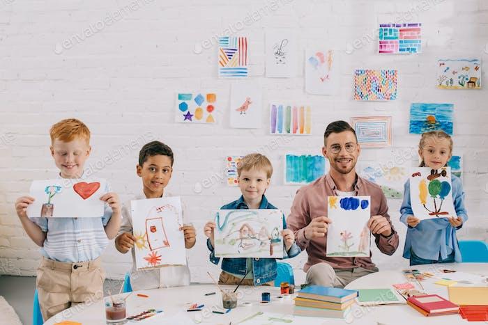 retrato de profesor sonriente y niños preescolares multiculturales que muestran coloridas imágenes en las manos