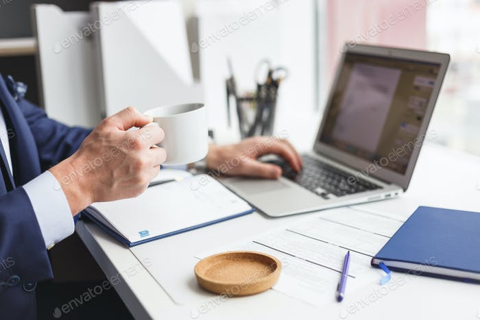 Businessman at work using laptop and drinking coffee