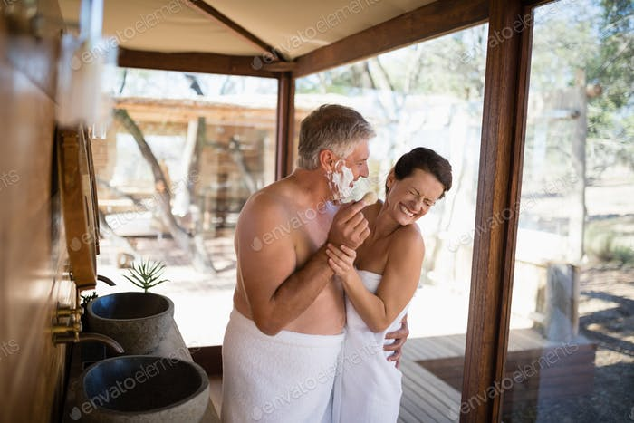 Smiling couple having fun while shaving in cottage