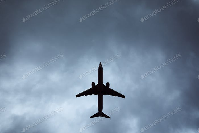 Silhouette of airplane in storm
