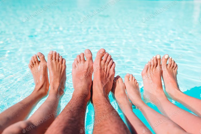 Close up of four people's legs by pool side