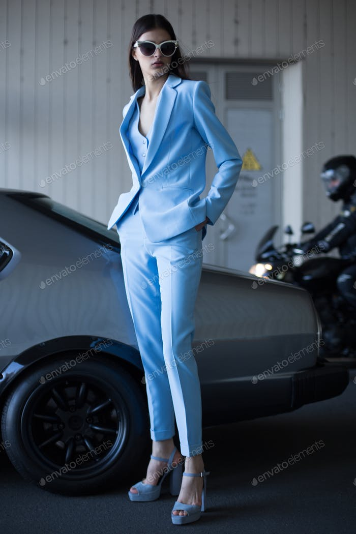 Stylish woman in a blue suit and sunglasses waiting near classic car at the parking