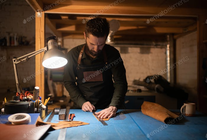 Bearded craftsman measuring leather in workshop