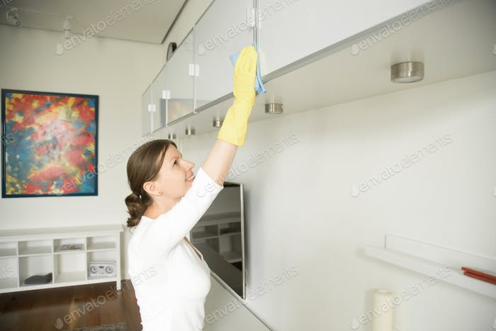 Young attractive woman cleaning an upper surface of the shelf