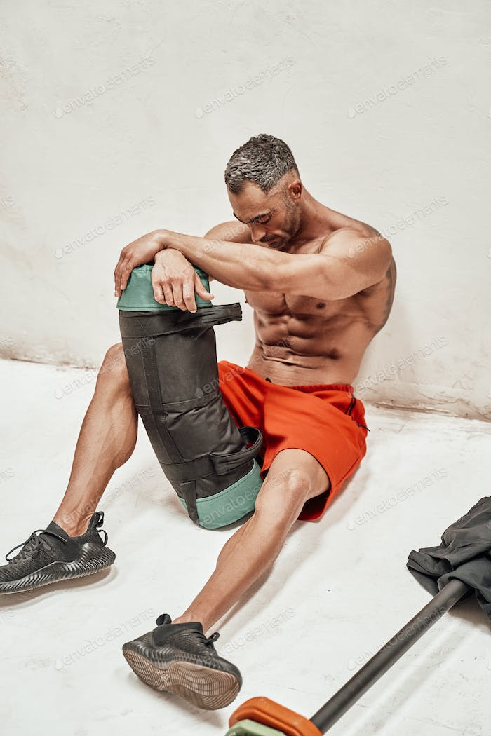 Handsome adult sportsman wearing sportswear posing for a camera while holding a weight bag