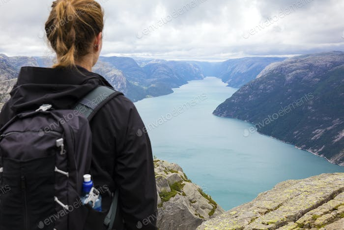 Female hiker standing at a high mountain in fjord