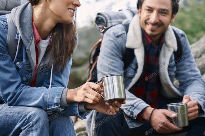 Two backpackers drinking coffee and talking