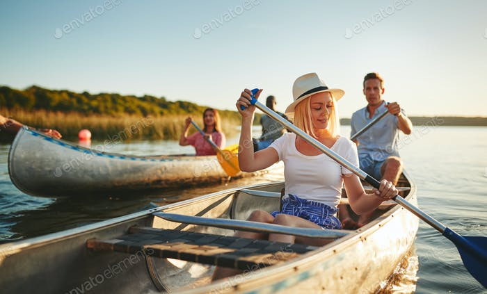 Smiling young woman canoeing with friends on a sunny afternoon