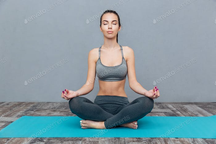 Girl practicing yoga isolated on a grey background
