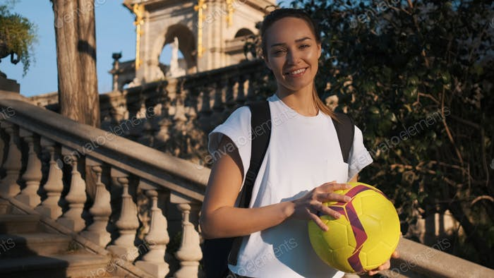 Beautiful girl with backpack and football happily looking in camera in park with architecture