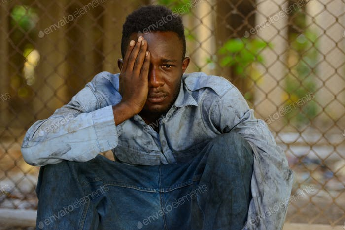 Young homeless African man looking depressed in the streets