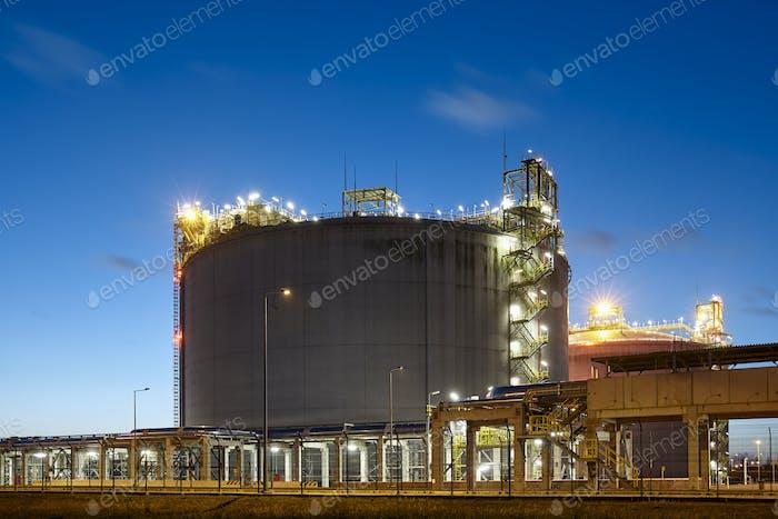 Liquefied natural gas storage tank at dusk.