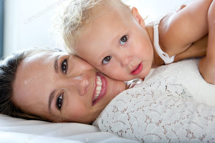 Beautiful mother smiling with cute baby girl