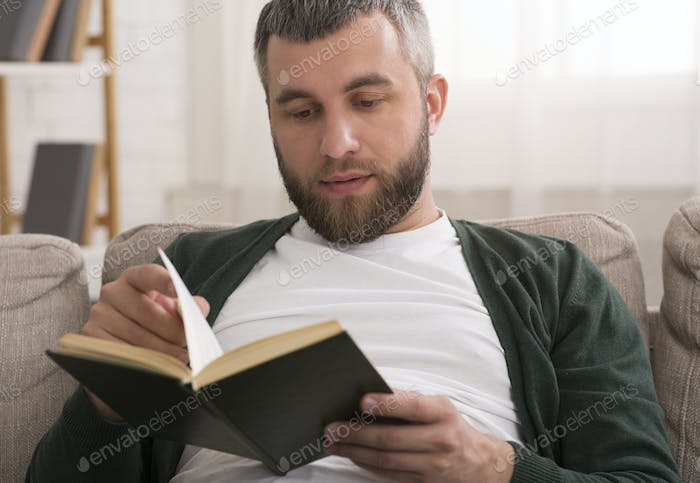 Middle aged man reading book at home