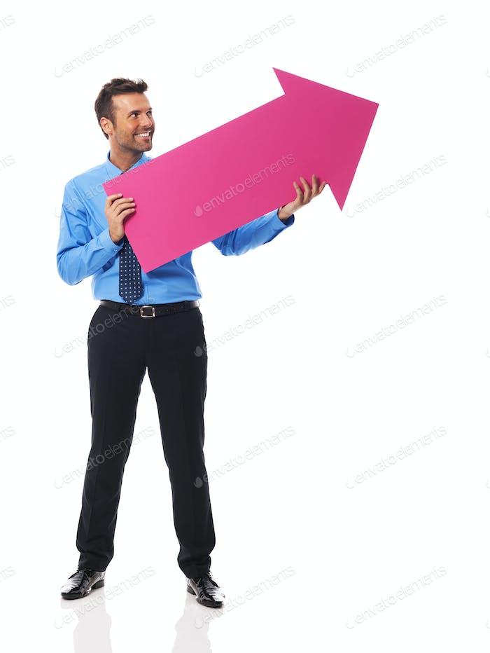 Hübscher Geschäftsmann hält rosa Pfeil und zeigt auf Kopie Raum