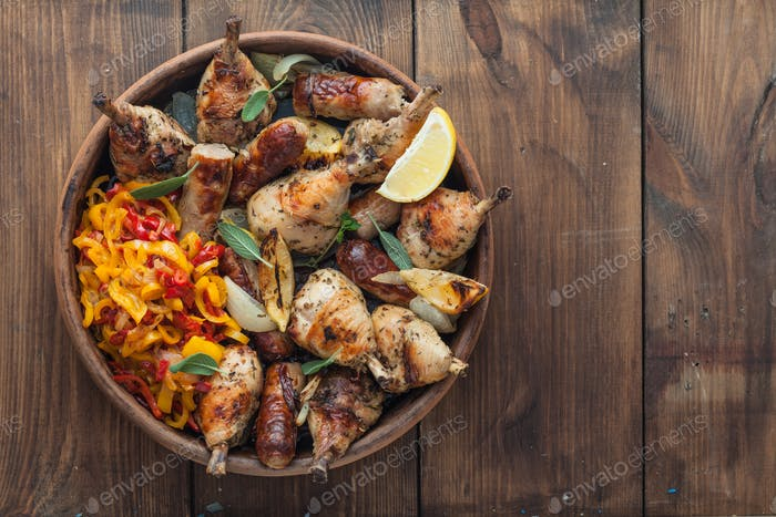 Baked chicken legs with sausages, sage and lemon. Top view. Copyspace