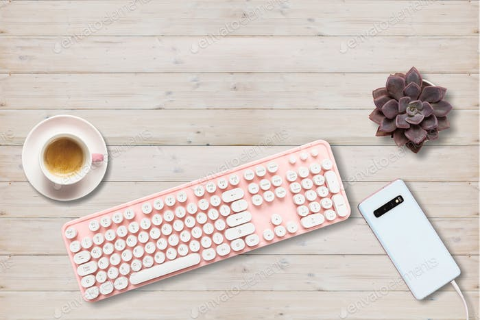 Computer keyboard pink color and smartphone against wood background
