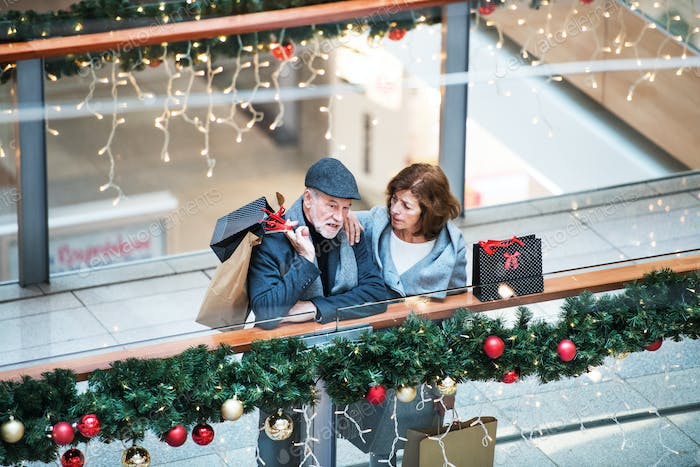 A senior couple with paper bags in shopping center at Christmas time.