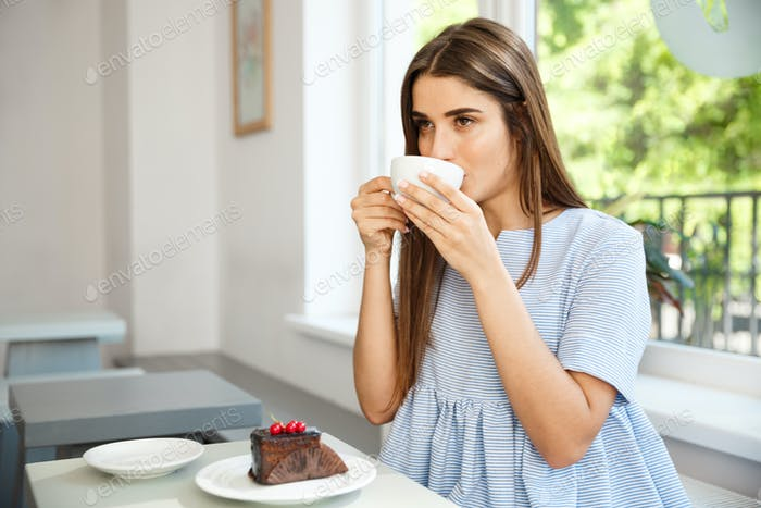 Young beautiful Caucasian lady enjoy drinking and having dessert in modern coffee shop at noon