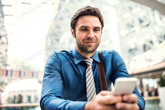 A young businessman with smartphone standing in a modern building, texting.