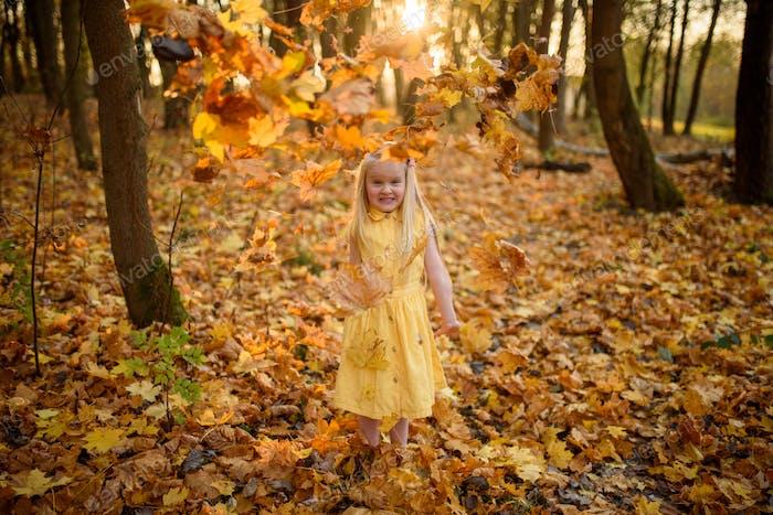 Niña pequeña con un vestido amarillo en el parque de otoño. El niño lanza hojas.