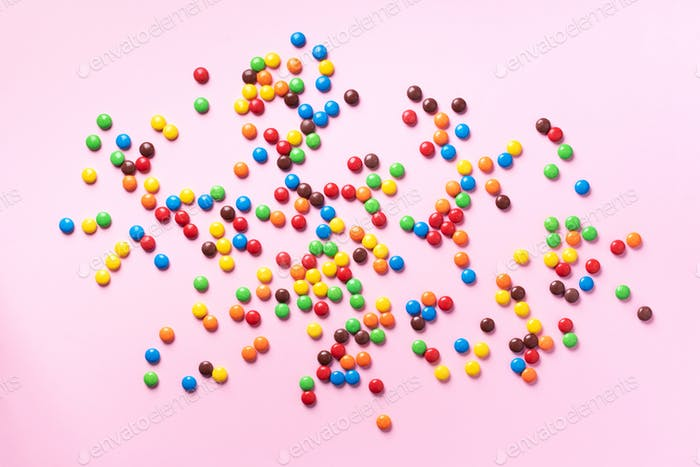 Rainbow colorful candies on pink background. Coated chocolate sweet pieces texture. Top view. Flat