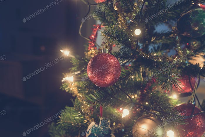 Retro image of shiny red Christmas bauble hanging on tree