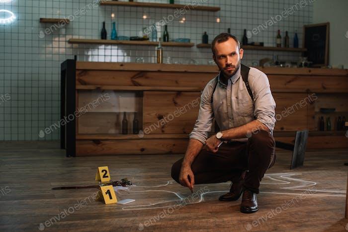 nachdenklicher männlicher Detektiv sitzt am Tatort