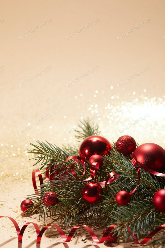 red sparkling christmas toys, wavy ribbon and pine branch on glittering surface
