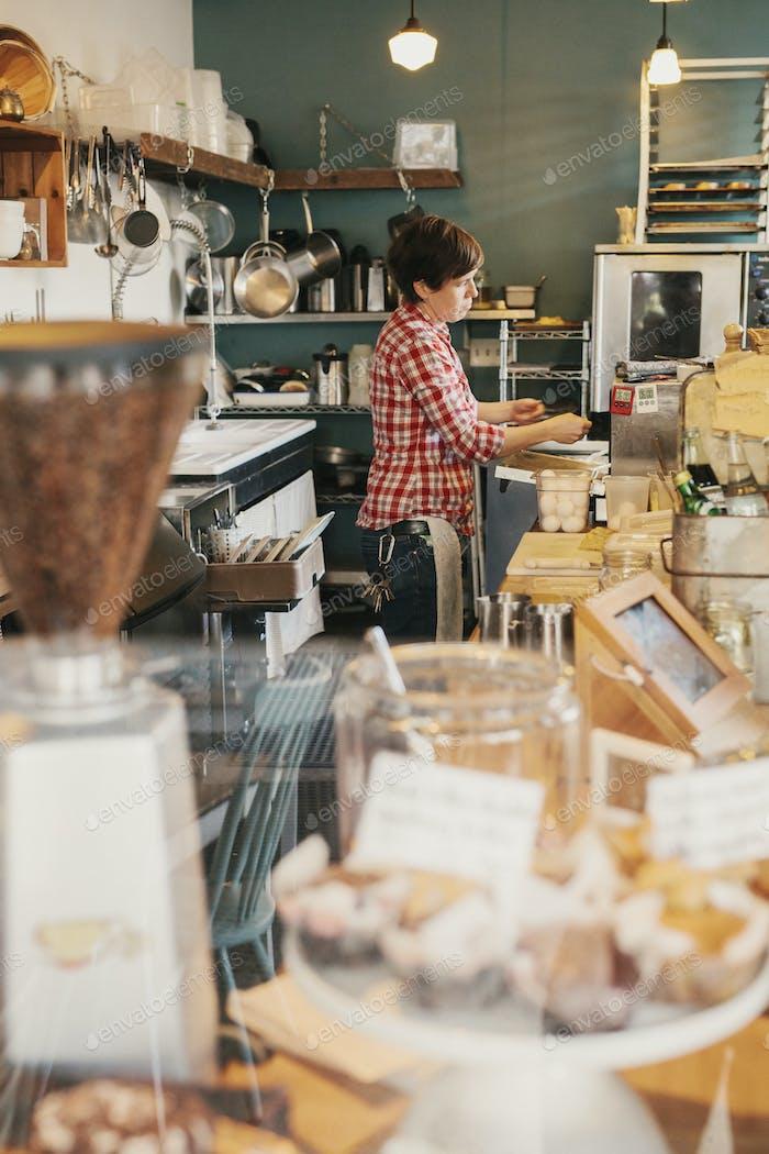 Eine Frau in einem karierten Hemd arbeitet hinter der Theke in einem Café.