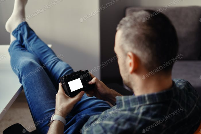 Photographer hold digital camera looking at white display