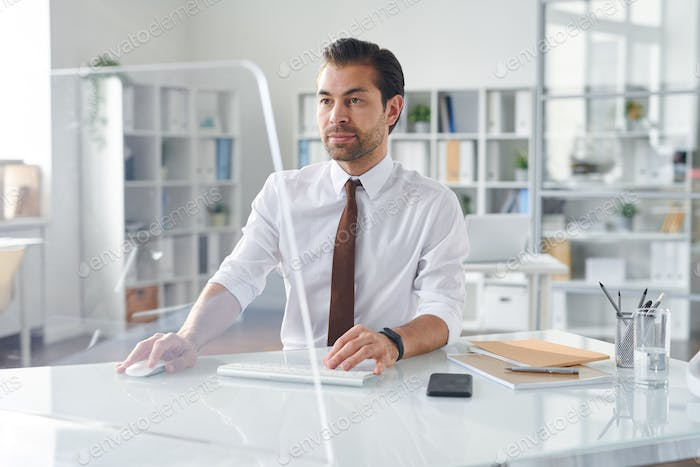 Young business analyst looking at computer screen by desk