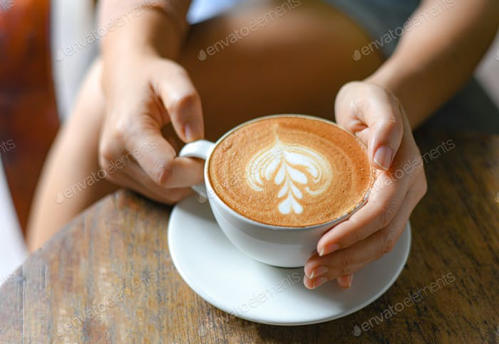 Women's hand holding a cup of coffee latte heart shaped leaves texture on wooden table.