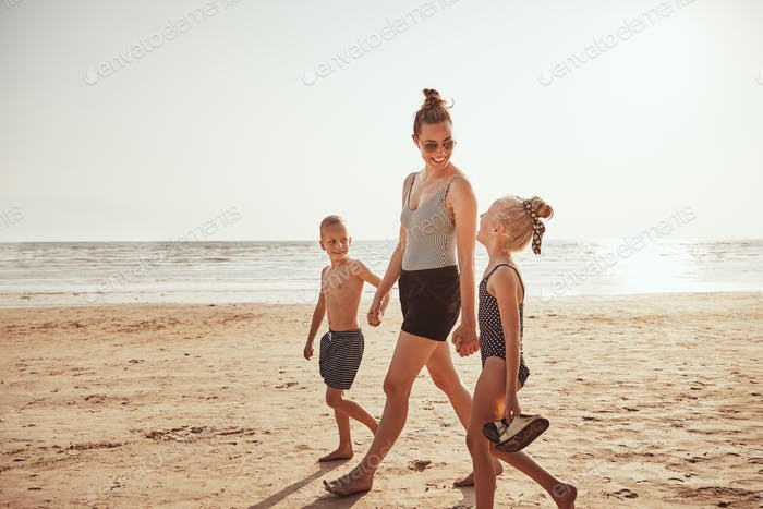 Smiling Mom and her kids walking along a sandy beach