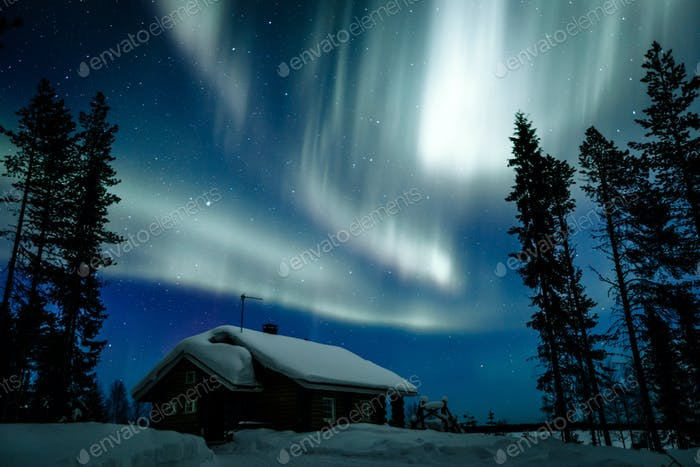 Northern lights Aurora Borealis activity over wooden cottage in winter Finland
