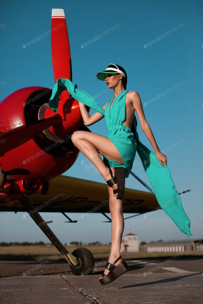 Beautiful fashion model girl in a visor posing next to propeller plane at runway during sunset