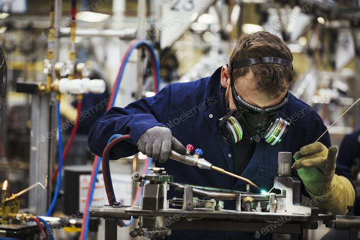 A man in a facemask with breathing filters, a skilled factory worker welding arts of a bicycle in a
