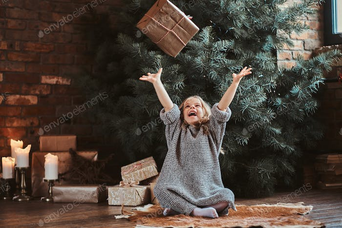 Portrait of cute little girl near christmas tree
