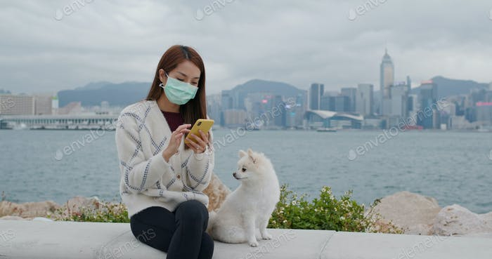 Frau tragen Gesichtsmaske Verwendung von Handy mit ihrem Hund im Freien